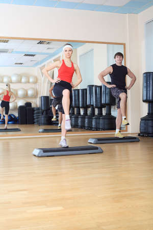 step fitness: Couple of a sporty young people in the gym centre. Stock Photo
