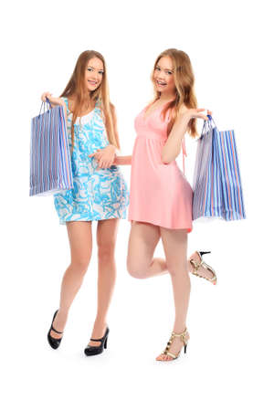 Two girls with shopping bags. Isolated over white background. photo