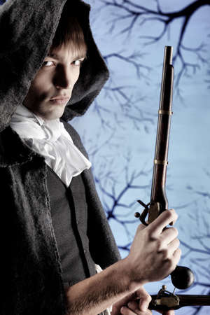 dinner jacket: Portrait of a young gentlemen in a dinner jacket and cloak holding guns in his hands. Shot in a studio.