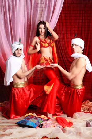 harem: Shot of three young people in oriental costumes.  Stock Photo
