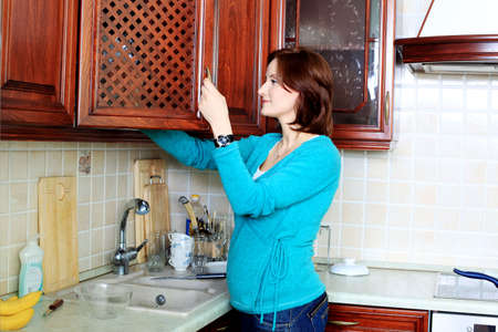 Young pregnant woman cooking meals at home. Stock Photo - 11692255