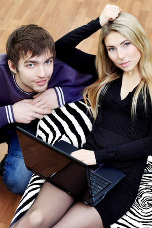 Young couple having a rest with a laptop at home. photo