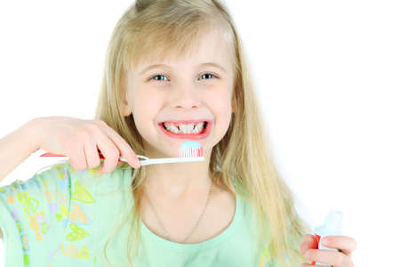Portrait of a little girl cleaning her teeth with a tooth brush. Isolated over white background.  photo