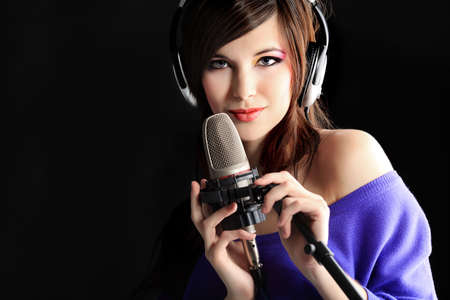 song: Shot of a pretty young woman in headphones singing a song with a microphone. Shot in a studio.