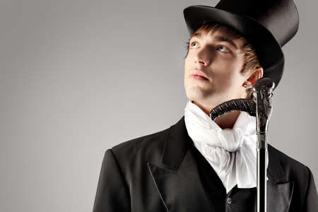 superiors: Portrait of a young gentlemen wearing dinner jacket and black top hat. Shot in a studio.