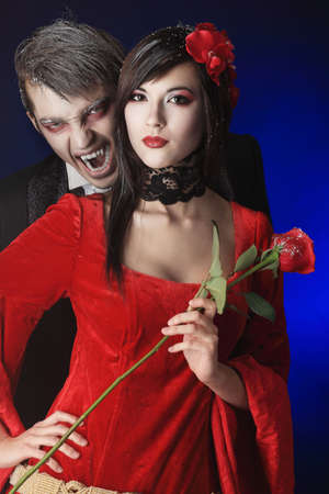 seductive couple: Portrait of a beautiful couple in medieval costumes with vampire style make-up. Shot in a studio. Stock Photo