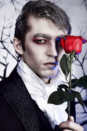 roses and blood: Portrait of a handsome young man with vampire style make-up. Shot in a studio. Stock Photo