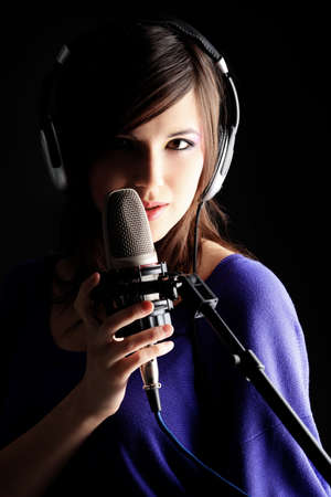 Shot of a pretty young woman in headphones singing a song with a microphone. Shot in a studio.