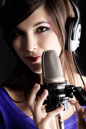 to sing: Shot of a pretty young woman in headphones singing a song with a microphone. Shot in a studio.