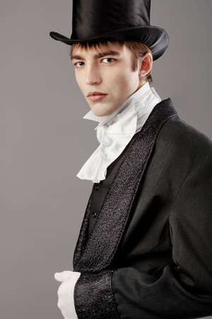 19th century: Portrait of a young gentlemen wearing dinner jacket and black top hat. Shot in a studio.