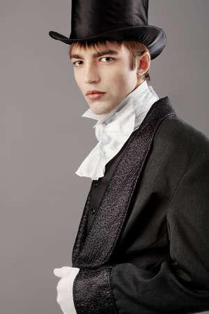 Portrait of a young gentlemen wearing dinner jacket and black top hat. Shot in a studio. Stock Photo - 6798907