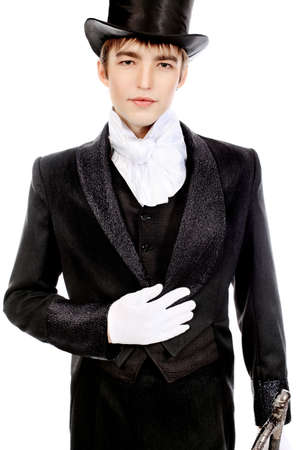 costume ball: Portrait of a young gentlemen wearing dinner jacket and black top hat. Shot in a studio.
