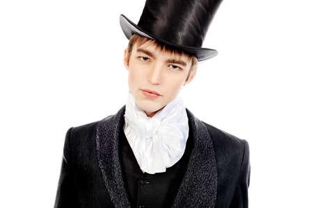 dinner jacket: Portrait of a young gentlemen wearing dinner jacket and black top hat. Shot in a studio.
