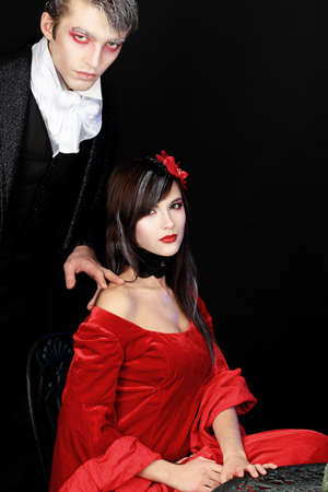 Portrait of a beautiful couple in medieval costumes with vampire style make-up. Shot in a studio. photo