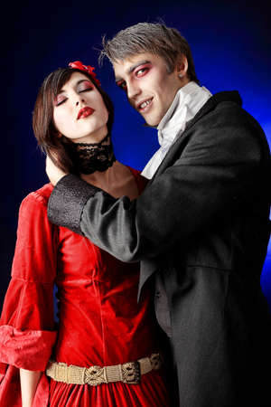 dracula woman: Portrait of a beautiful couple in medieval costumes with vampire style make-up. Shot in a studio. Stock Photo