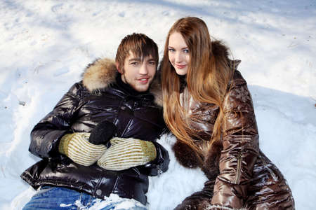 Portrait of a young couple having a rest in winter park. photo