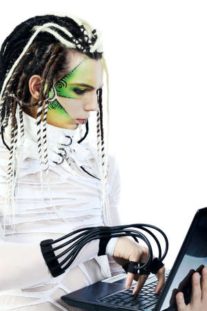 Shot of a futuristic young man with wires holding a laptop. Isolated over white background. photo