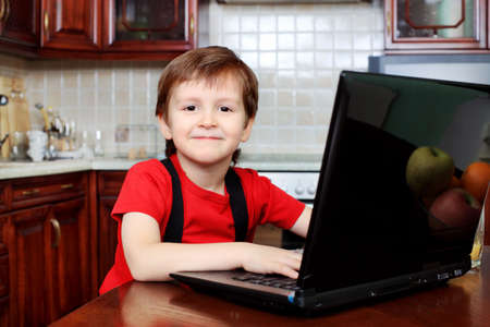 living room boy: Little boy with his laptop at home. Stock Photo