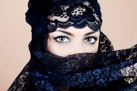 Shot of a beautiful asian woman with black veil on face, traditional arabian costume.