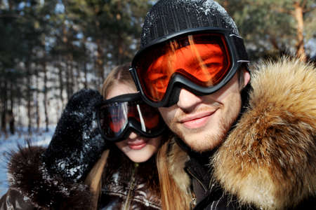 tourist resort: Portrait of a happy young couple having a rest in winter park.