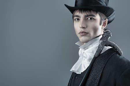 Portrait of a young gentlemen wearing dinner jacket and black top hat. Shot in a studio. photo