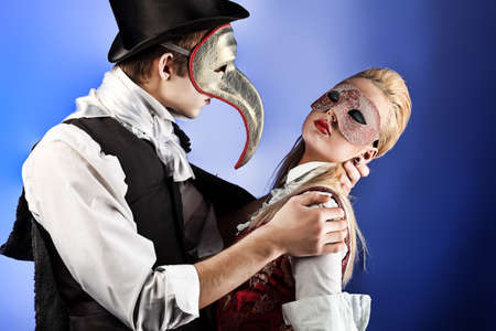 costume ball: Portrait of the elegant young couple in masquerade costumes. Shot in a studio.