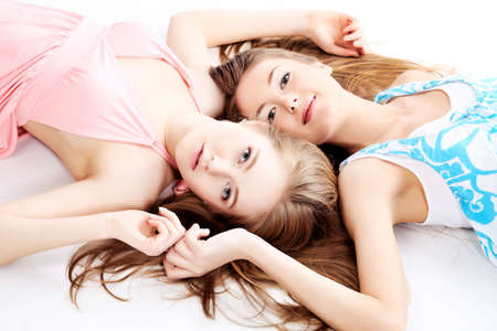 Two happy girls friends. Isolated over white background. photo