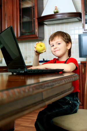 Little boy with his laptop at home. Stock Photo - 11692152