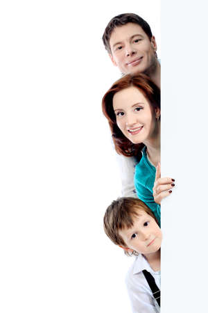 Portrait of a happy family looking out of a billboard. Isolated over white background. Stock Photo - 6902708