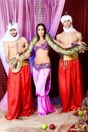 Shot of young people in oriental costumes posing with a python.  photo