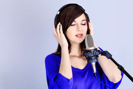 Shot of a pretty young woman in headphones singing a song with a microphone. Shot in a studio.  photo