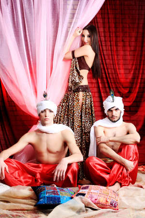 Shot of three young people in oriental costumes.  photo
