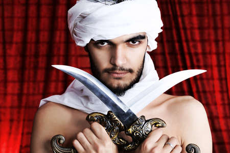 turban: Shot of a man in oriental costume holding daggers. Stock Photo