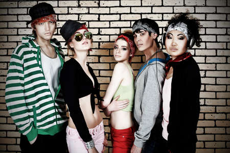 Group of trendy teenagers posing together against a brick wall. Stock Photo - 7029249