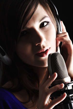 музыкант: Shot of a pretty young woman in headphones singing a song with a microphone. Shot in a studio.