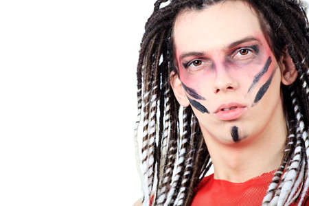 Artistic young man with dreadlocks and red make-up. Shot in a studio. photo