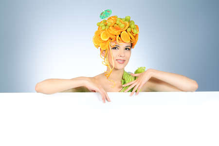 Shot of a beautiful young woman with fruits headwear holding white board. Food concept, healthcare. Stock Photo - 7096137