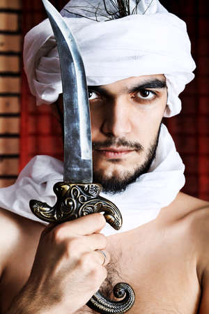 sultan: Shot of a man in oriental costume holding daggers. Stock Photo