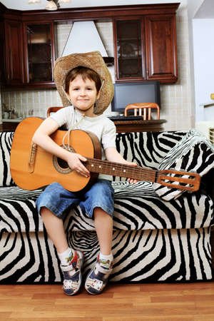 Shot of a little boy playing his guitar at home. photo