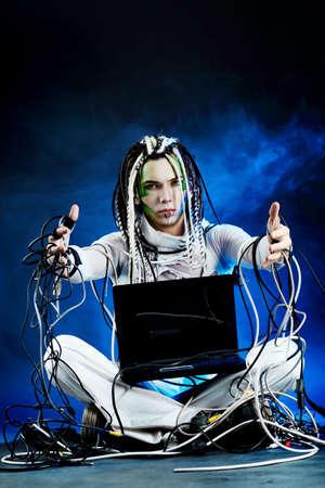 dreadlocks: Disparo de un hombre joven futuro sentado con un ordenador port�til y cables.