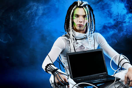 Shot of a futuristic young man sitting with a laptop and wires. Stock Photo - 7344920
