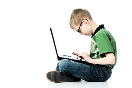 Shot of a Boy sitting mit seinem Laptop. Isolated over white Background.