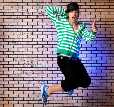 Shot of a jumping over brick background young man. photo