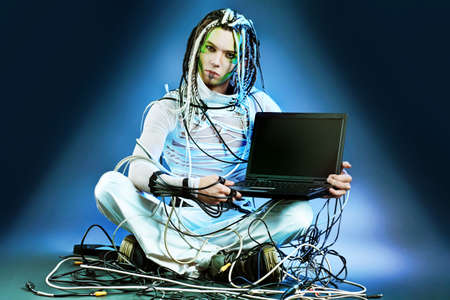 Shot of a futuristic young man sitting with a laptop and wires. photo