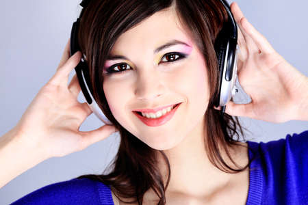 Shot of a pretty young woman in headphones listening to music with pleasure. Shot in a studio.  photo