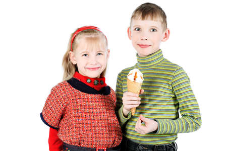 Little boy and girl are eating an ice-cream. Isolated over white background. photo
