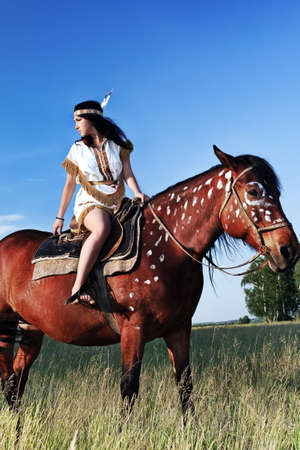 cowgirl and cowboy: Beautiful young woman posing with a brown horse.