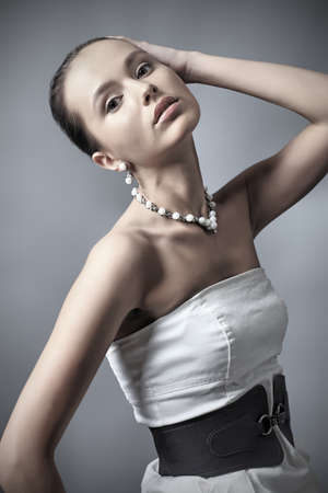 vogue: Fashion photo, a model is  posing over grey background