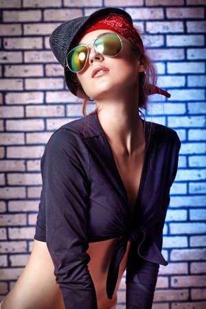 Trendy Mädchen Teenager posing gegen eine Mauer.