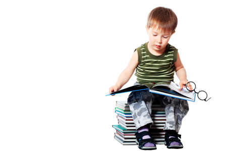 Portrait of a cute little boy with books. Isolated over white background. photo